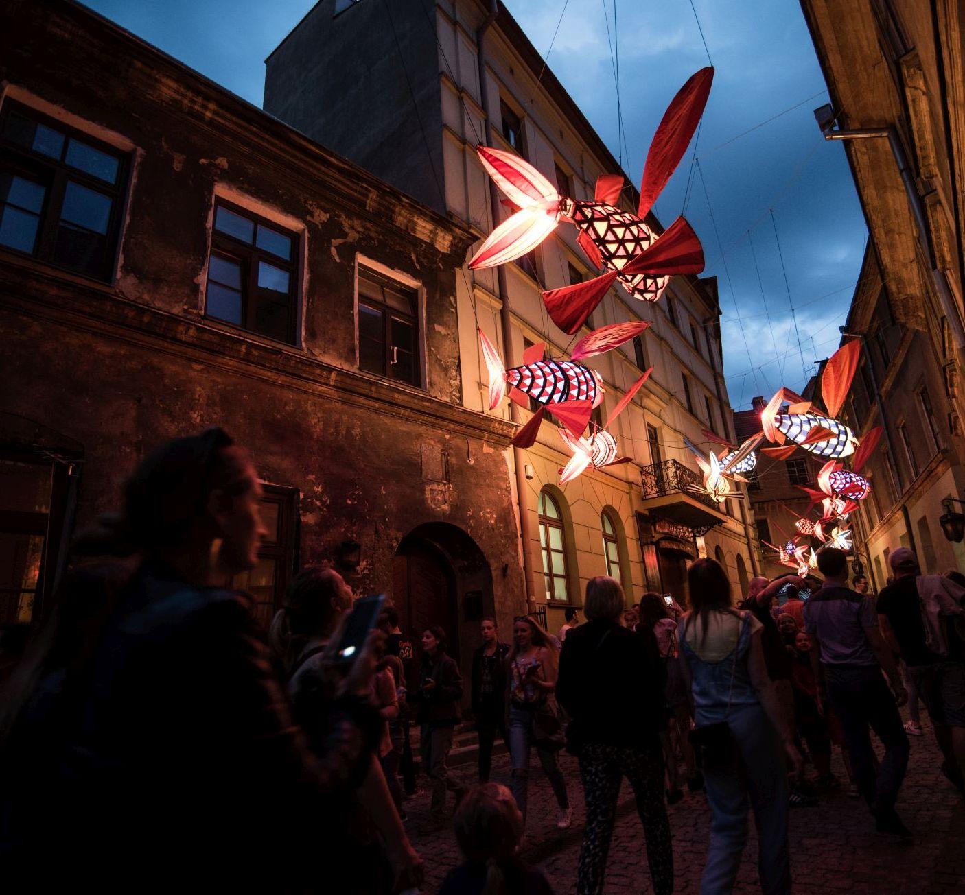 tłum na ulicy Starego Miasta w Lublinie. ponad głowami spacerujących zawieszone duze kolorowe, podświetlone ryby